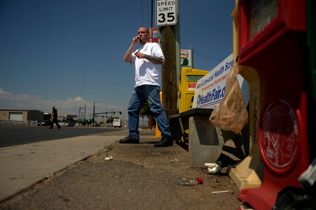 """. Parolee Thomas Vescio, 35, waits for a bus in the one town he was hoping to avoid, Commerce City, on July 11, 2013. \""""Everyone knows me here,\"""" he said. He has lived here all his life and this is where his troubles began and continued. He asked to be moved but was told this was the only opening.  (Photo By Joe Amon/The Denver Post)"""