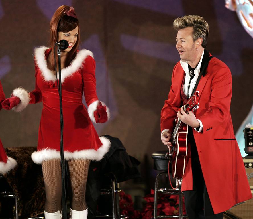 . Musician Brian Setzer plays near one of his singers at the Rockefeller Center Christmas tree lighting in New York\'s Rockefeller Plaza, Wednesday, Nov. 30, 2005.   (AP Photo/Jeff Christensen)