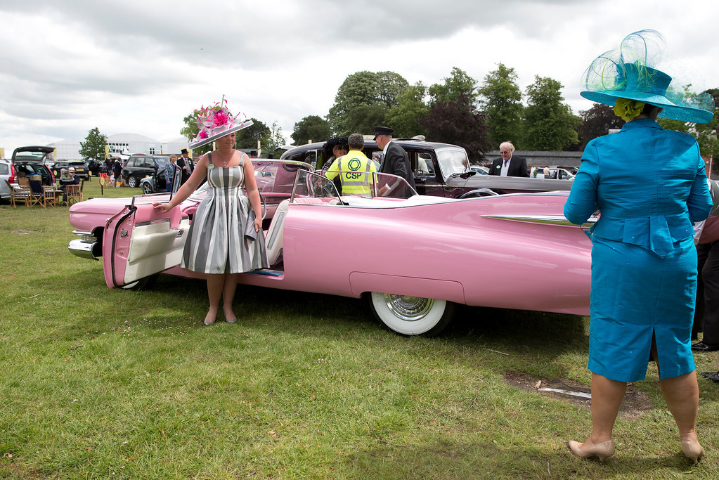 . Olivia Giles, left poses for a photograph taken by her mother Tracey in front of a 1959 series 62 Cadillac open top car in a scar park on the second day of the Royal Ascot horse racing meeting at Ascot, England,  Wednesday, June, 18, 2014. (AP Photo/Alastair Grant)