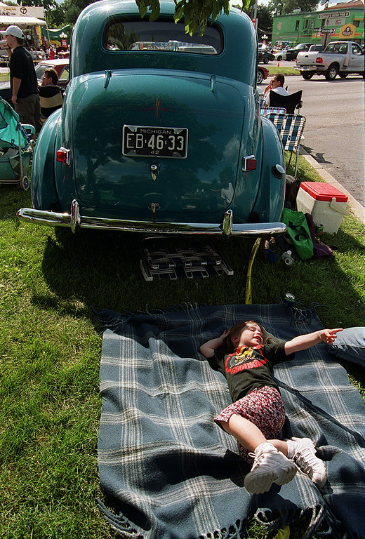 . A sleepy Samantha Jensen, 4, tries to nap on a blanket behind her grandpa\'s 1942 Willys during the Woodward Dream Cruise saturday afternoon.