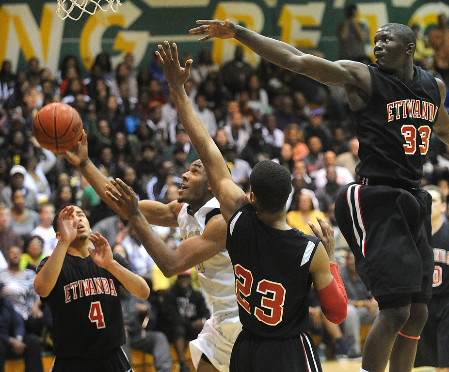 . 02-26-2012--(LANG Staff Photo by Sean Hiller)- Long Beach Poly hosts Etiwanda in Tuesday\'s CIF Southern Section Division 1AA semifinal boys basketball game at Long Beach Poly High School. Poly\'s Roschon Prince (1) battles Etiwanda\'s Dominick Alexander (4) ,left, Kenny Barnes (23) and Tim Myles (33).