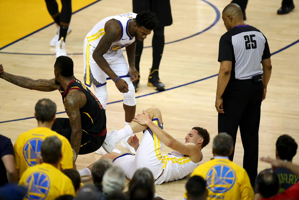 . Golden State Warriors guard Klay Thompson, bottom, is checked on by forward Jordan Bell during the first half of Game 1 of basketball\'s NBA Finals against the Cleveland Cavaliers in Oakland, Calif., Thursday, May 31, 2018. (AP Photo/Ben Margot)