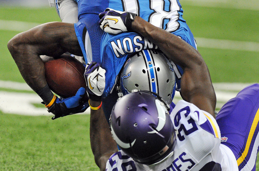 . Vikings cornerback Xavier Rhodes tackles Lions wide receiver Calvin Johnson after a reception in the second quarter.  (Pioneer Press: Chris Polydoroff)