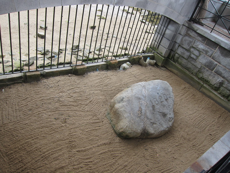 The famous Plymouth Rock of colonial times sits on the sandy surface of a fenced area in Plymouth, Massachusetts