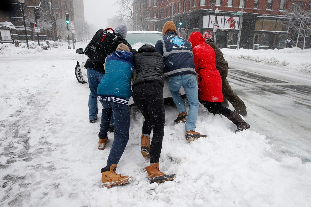 . People push a stranded taxi during a snowstorm, Tuesday, March 13, 2018, in Boston.  The third major nor�easter in two weeks slammed New England on Tuesday, bringing blizzard conditions and more than a foot of snow to some communities.   (AP Photo/Michael Dwyer)