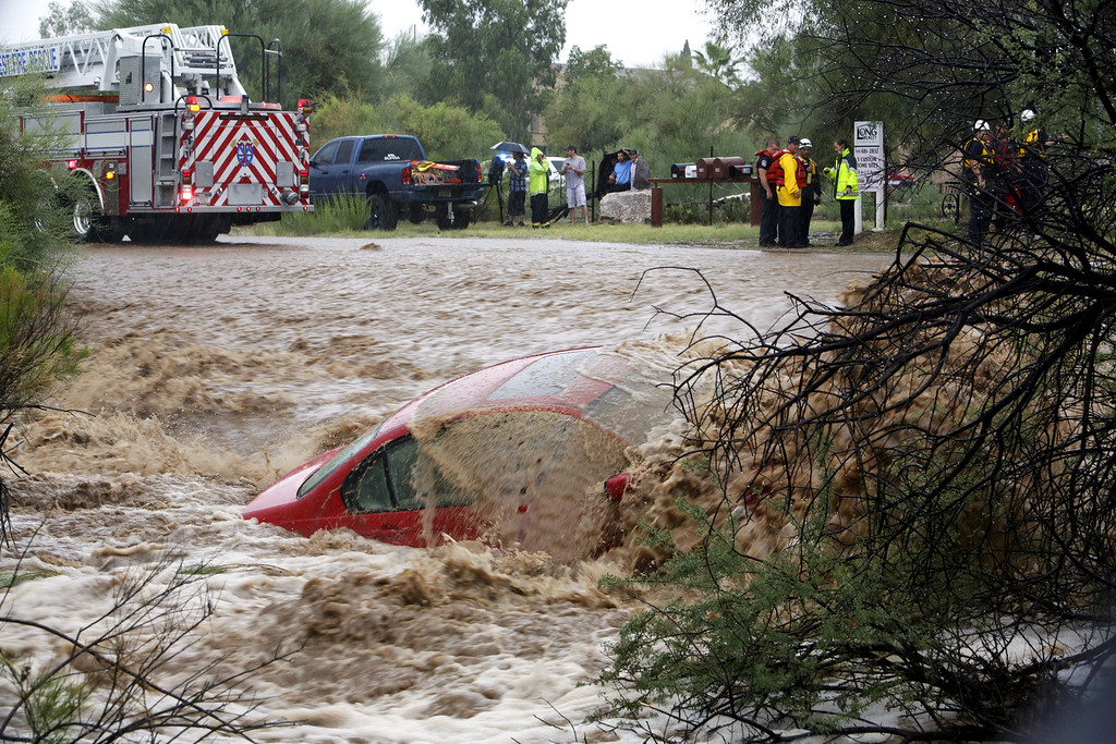 . Water washes over the car after the driver was rescued by members of Northwest Fire District north of Tucson, Ariz., on Monday, Sept. 8, 2014. The Phoenix and Tucson metro areas were hit by heavy rains, causing flooding and damage. More than 3 inches of rain closed parts of several Phoenix freeways. In Tucson, the National Weather Service recorded nearly 2 inches of rain. (AP Photo/Arizona Daily Star, Ron Medvescek)