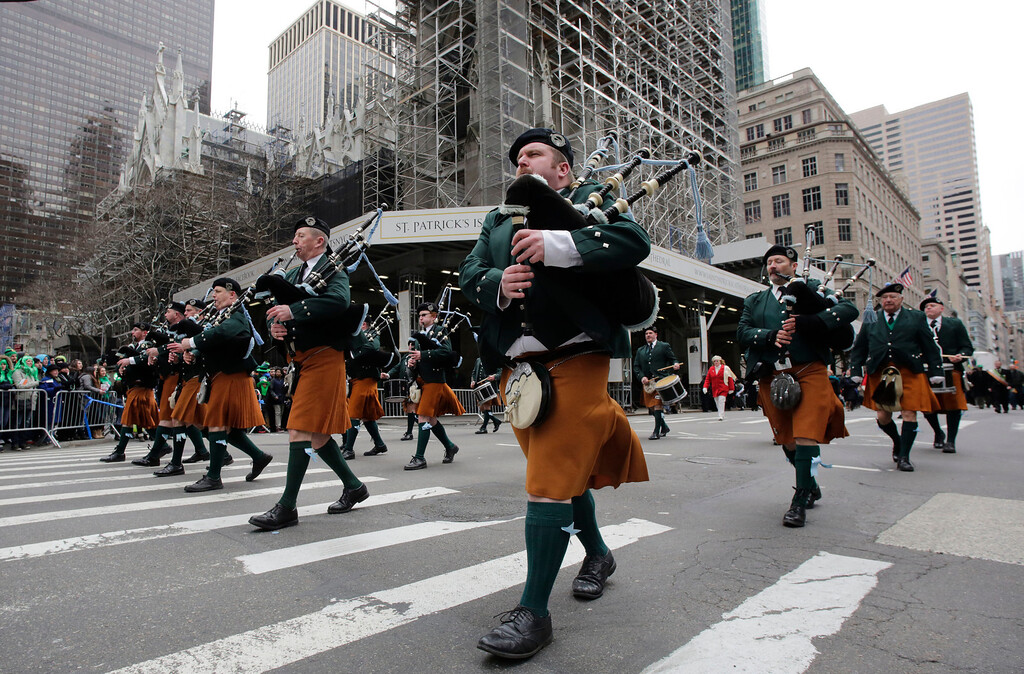 . The County Tyrone Pipe Band marches in the St. Patrick\'s Day parade, Monday, March 17, 2014 in New York. St. Patrick\'s Cathedral, center, is wrapped in scaffolding for renovations. (AP Photo/Mark Lennihan)