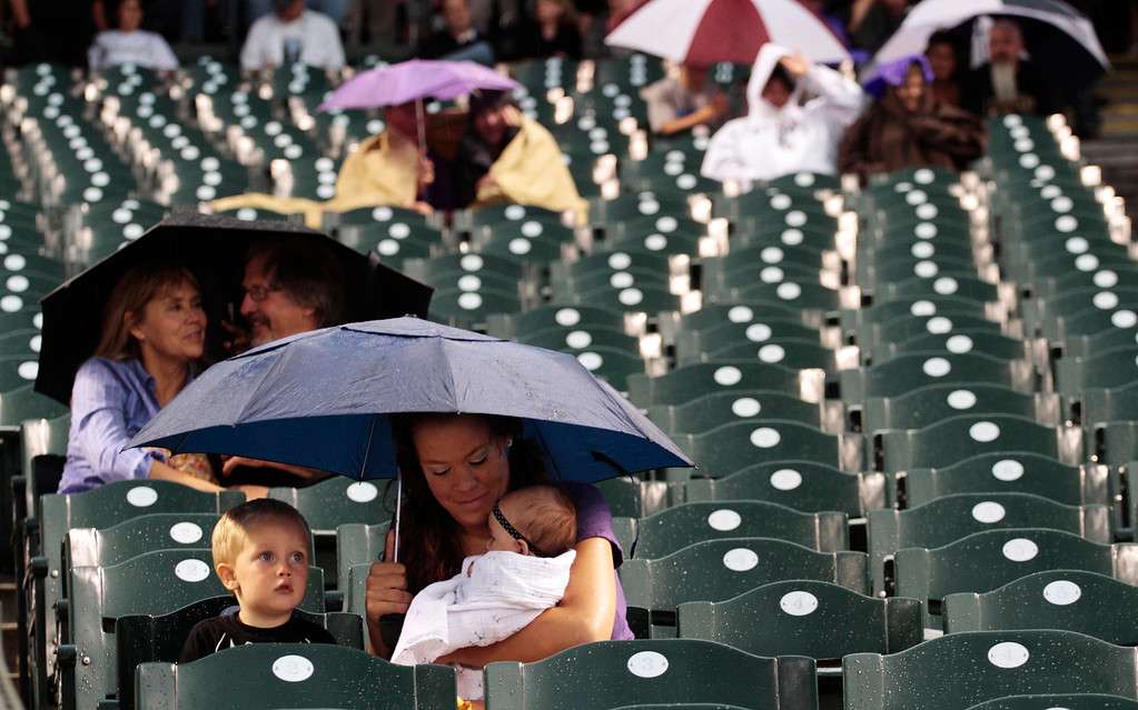 . Tawney Summers, of Fort Collins, Colo., holds her 4-month-old daughter, Ema, as they huddle with her son, Maddock, 2, during a rain storm that delayed the Colorado Rockies against the PIttsburgh Pirates baseball game in Denver on Saturday, Aug. 10, 2013. (AP Photo/Joe Mahoney)