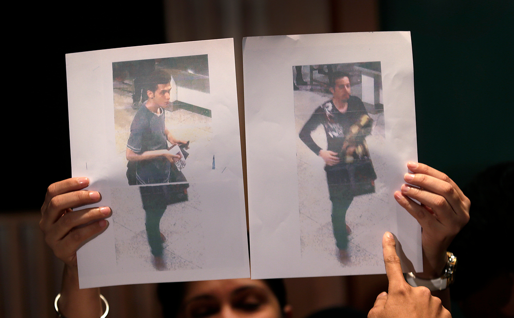 . Pictures of the two men, a 19-year old Iranian, identified by Malaysian police as Pouria Nour Mohammad Mehrdad, left, and the man on the right, his identity still not released, who boarded the now missing Malaysia Airlines jet MH370 with stolen passports, is held up by a Malaysian policewoman during a press conference, Tuesday, March 11, 2014 in Sepang, Malaysia. One of the two men traveling on a missing Malaysian Airlines jetliner was an Iranian asylum seeker, officials said Tuesday, as baffled authorities expanded their search for the Boeing 777 on the opposite side of the country from where it disappeared nearly four days ago with 239 people on board. (AP Photo/Wong Maye-E)