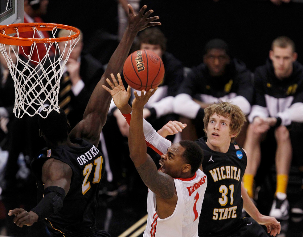 . Ohio State Buckeyes forward Deshaun Thomas (C) goes to the basketb between Wichita State Shockers\' Ehimen Orukpe (21) and Ron Baker (31) during the first half of their West Regional NCAA men\'s basketball game in Los Angeles, California March 30, 2013. REUTERS/Alex Gallardo