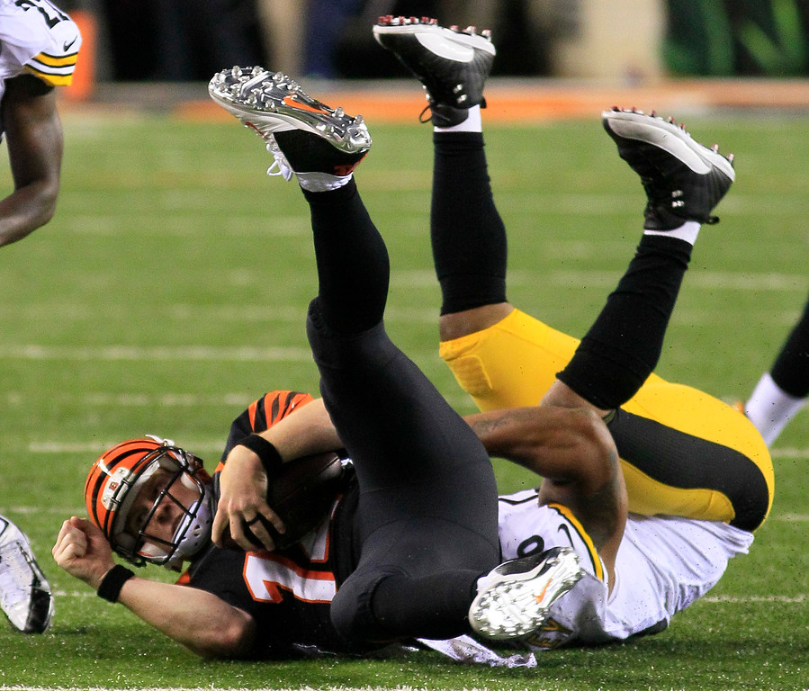 . Cincinnati Bengals quarterback Andy Dalton, left, is tackled after a short gain by Pittsburgh Steelers outside linebacker LaMarr Woodley in the second half of an NFL football game, Monday, Sept. 16, 2013, in Cincinnati. (AP Photo/Tom Uhlman)