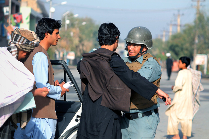 . An Afghan policeman frisks men at a check point on the streets of Kandahar on April 5, 2014. Afghan voters went to the polls to choose a successor to President Hamid Karzai, braving Taliban threats in a landmark election held as US-led forces wind down their long intervention in the country.  (JAVED TANVEER/AFP/Getty Images)