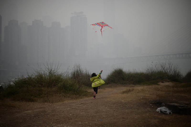 . A picture made available 24 February 2014 shows a little girl flying a kite on the river bank in the smog in southwest Chongqing Municipality, China, 23 February 2014. Due to smog alerts, a city in northern China has banned a fifth of residents\' vehicles from roads, reports stated since 23 February. In Beijing, an orange alert had been issued on 21 February due to smog which is the second-highest of four levels of urgency. The Environmental Protection Ministry has sent 12 inspection teams to Beijing, Tianjin, Hebei and surrounding areas to check on compliance to measures to reduce air pollution.  (EPA/RAN WEN)