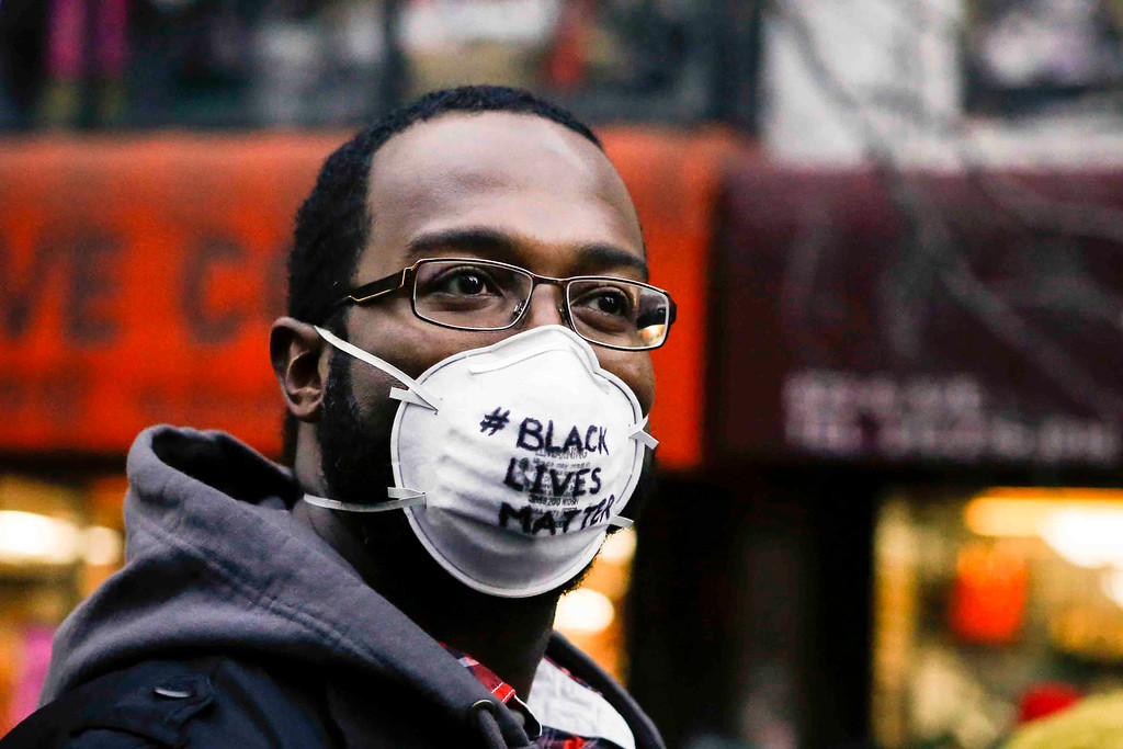 . A man with a dust mask on marches in the National March Against Police Violence, which was organized by National Action Network, down 14th St on December 13, 2014 in New York City. The march coincided with a march in Washington D.C. and comes on the heels of two grand jury decisions not to indict white police officers in the deaths of two unarmed black men. (Photo by Kena Betancur/Getty Images)