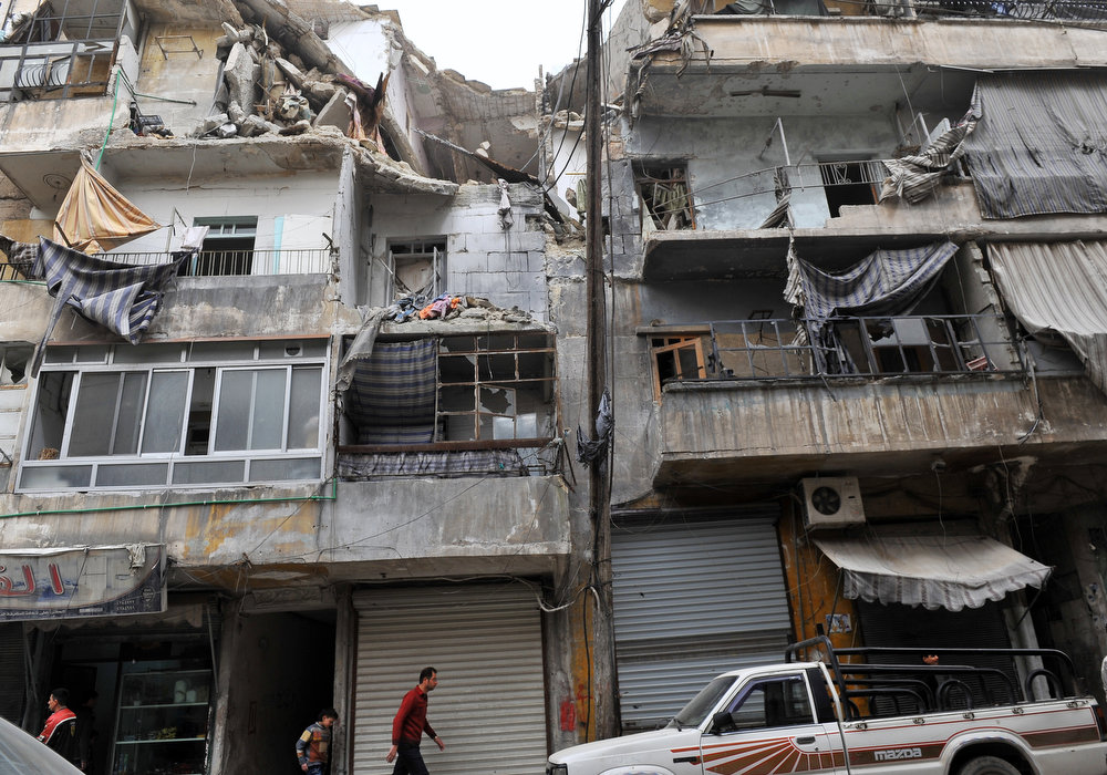 . Syrians walk past a partially destroyed building in the northern city of Aleppo on March 22, 2013. The UN lamented the escalating violence in Syria and extended a probe into widespread human rights violations in the war-torn country. AFP PHOTO/BULENT KILIC