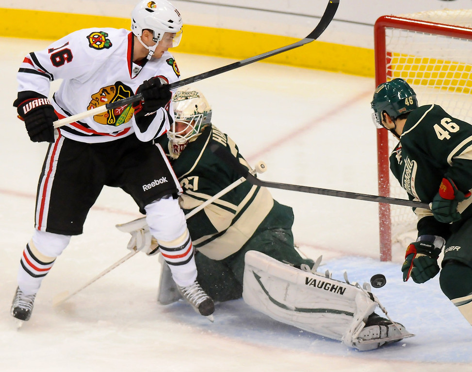 . Minnesota goalie Josh Harding stops the puck while pushing Chicago center Marcus Kruger, left, out of the zone in the first period. Defending on the play is defenseman Jared Spurgeon, right. (Pioneer Press: John Autey)