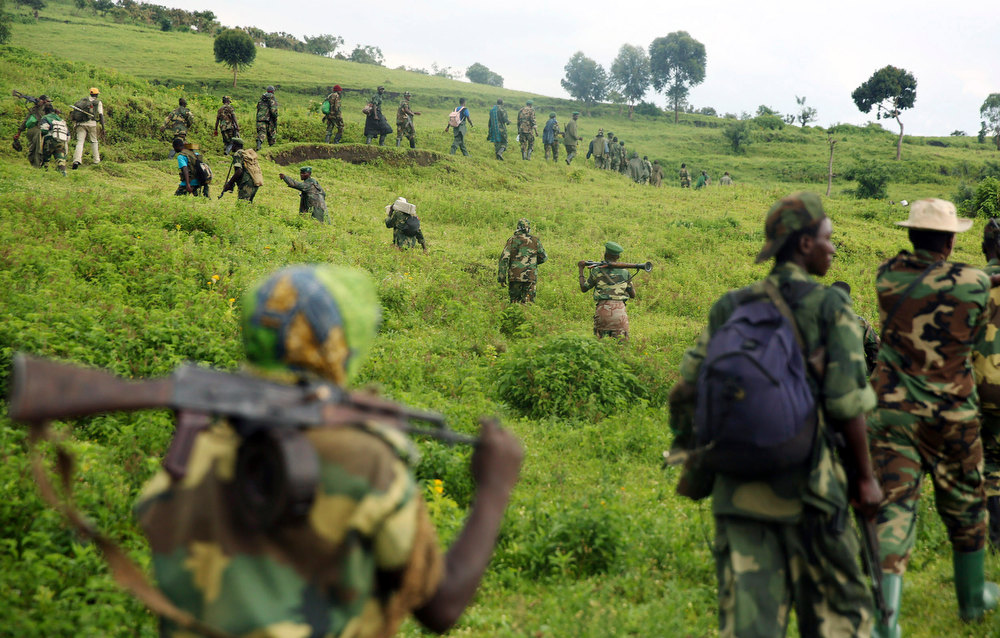 . M23 rebel fighters walk as they withdraw near the town of Sake, some 42 km (26 miles) west of Goma November 30, 2012. A rebel pullback from Goma, seized by M23 from fleeing United Nations-backed government forces on November 20, would signal some progress in international efforts to halt the eight-month-old insurgency in eastern Democratic Republic of Congo. REUTERS/Goran Tomasevic