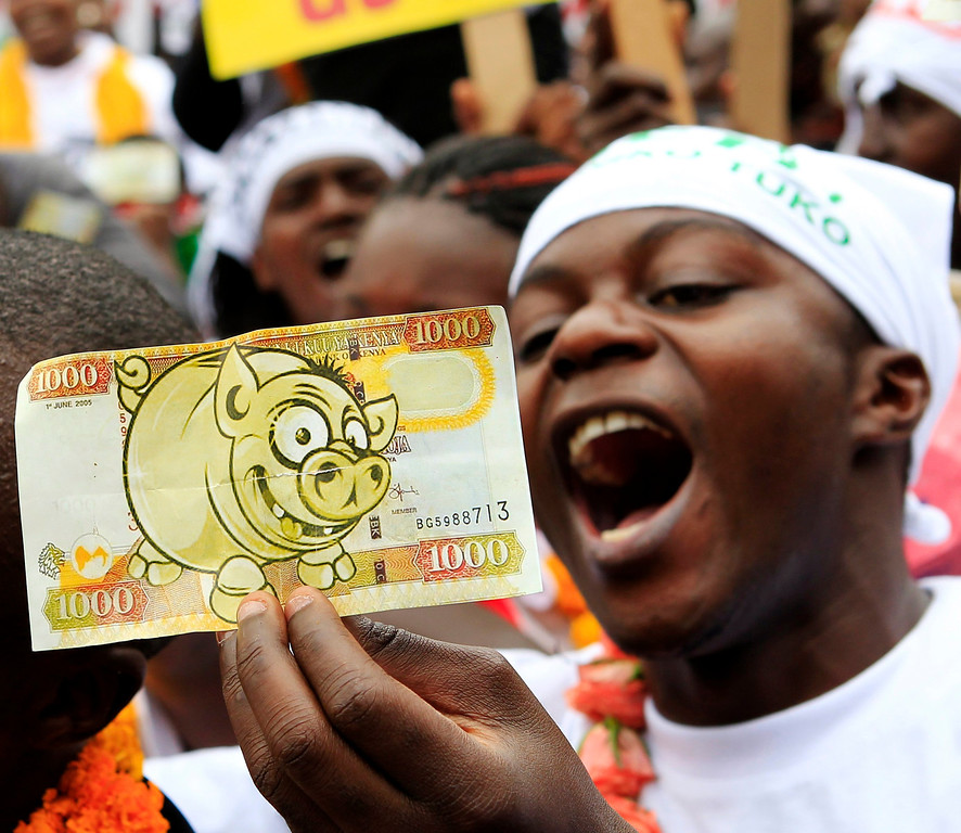 . A protester displays a modified Kenyan 1,000 Shilling note ($12) imprinted with an image of a pig to depict what he says is greed in lawmakers demanding for a pay rise, during a demonstration in Nairobi, June 11, 2013. Refusing to accept a cut imposed by the Salaries and Remuneration Commission in May, members of parliament voted to increase their salaries to 130 times the minimum wage, which according to them, are needed to deter bribery and provide charitable support for constituents. Protesters have deemed the proposed salary raise a violation of the constitution, according to news reports. REUTERS/Noor Khamis