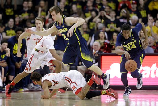 . Michigan guard/forward Aubrey Dawkins, right, drives the ball down the court as teammate Spike Albrecht (2) jumps over Maryland guard Melo Trimble in the first half of an NCAA college basketball game, Saturday, Feb. 28, 2015, in College Park, Md. (AP Photo/Patrick Semansky)