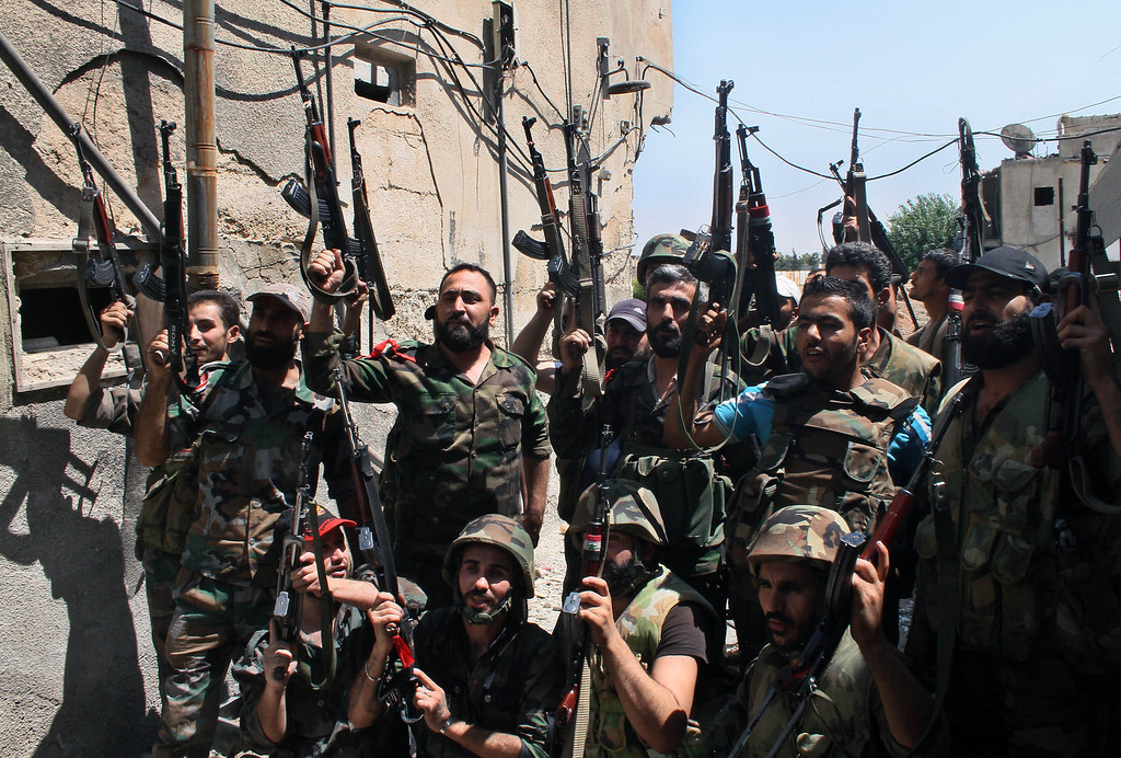 . In this Sunday, July 14, 2013 file photo, Syrian soldiers cheer after battling with rebels during a tour for journalists organized by the Syrian Information Ministry in the Damascus suburb of Jobar, Syria. More than two years into Syria\'s civil war, the once highly-centralized authoritarian state has effectively split into three distinct parts, each boasting its own flags, security agencies and judicial system. (AP Photo/Bassem Tellawi)