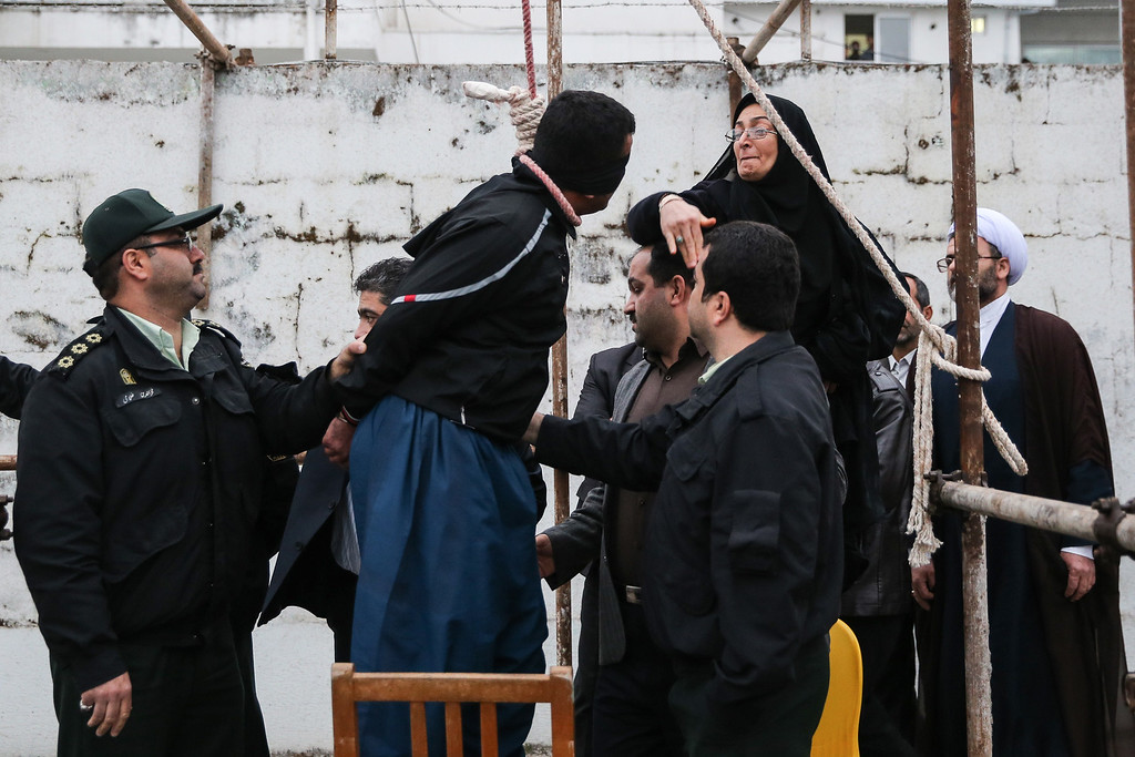 . The mother (R) of Abdolah Hosseinzadeh, who was murdered in 2007, slaps Balal who killed her son during the execution ceremony in the northern city of Nowshahr on April 15, 2014 just before she removed the noose around his neck with the help of her husband, sparing the life of her son\'s convicted murderer. The dramatic events followed a rare public campaign to save the life of Balal, who at 19 killed another young man, Abdollah Hosseinzadeh, in a street fight with a knife back in 2007. AFP PHOTO/ARASH KHAMOOSHI/AFP/Getty Images