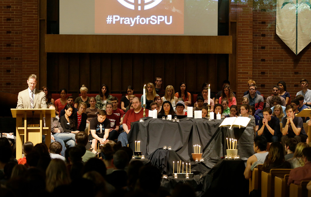 . Dan Martin, left, president of Seattle Pacific University, speaks at a prayer service at First Free Methodist Church on Thursday, June 5, 2014, at Seattle Pacific University in Seattle. A lone gunman armed with a shotgun opened fire  in a building at the small Seattle university, fatally wounding one person and injuring three others before a student subdued him with pepper spray as he tried to reload, Seattle police said. (AP Photo/Ted S. Warren)