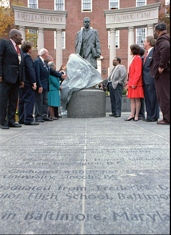 """. Maryland Gov. Parris Glendening pulls off the drape to unveil the Thurgood Marshall Memorial in Annapolis, Md. on Tuesday Oct. 22, 1996 as state officials and the late Supreme Court justice\'s family watch. The seven foot bronze statue stands on a granite pedestal in front of two fifteen-foot limestone columns inscribed \""""Equal Justice Under Law.\"""" Justice Marshall served 24 years on the court. He was born in Baltimore and was responsible for the desegregation law written in the case of Brown vs. the Board of Education. (AP Photo/Gary Sussman)"""