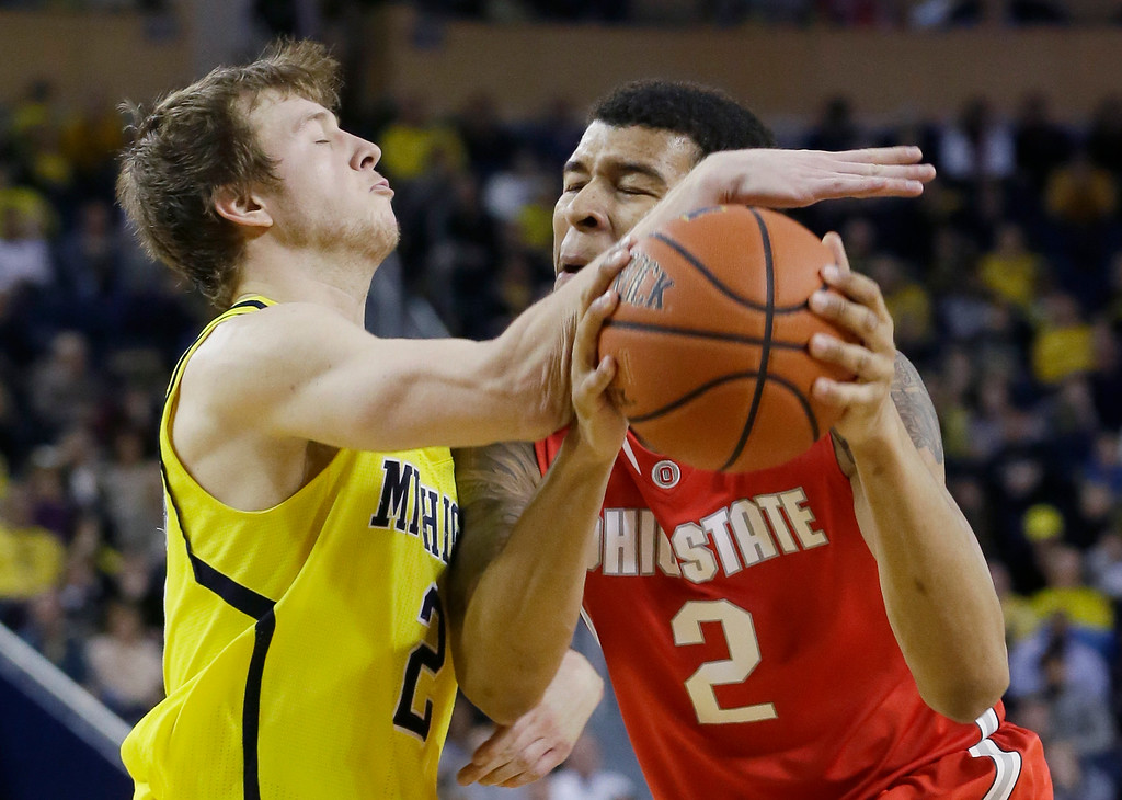 . Ohio State forward Marc Loving (2) is fouled by Michigan guard Spike Albrecht (2) during the second half of an NCAA college basketball game, Sunday, Feb. 22, 2015 in Ann Arbor, Mich. Michigan defeated Ohio State 64-57. (AP Photo/Carlos Osorio)