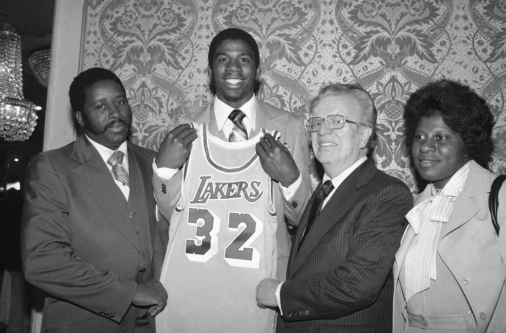 ". Earvin ""Magic\"" Johnson, second from left, beams as he holds a Los Angeles Lakers uniform at New York\'s Plaza Hotel, Monday, June 26, 1979 where he was selected by the Lakers in the first round of the National Basketball Association draft. \""Magic\"" is joined by NBA Commissioner Larry O\'Brien, second from right, and by his parents, Mr. and Mrs. Earvin Johnson, left and right, respectively. (AP Photo/Marty Lederhandler)"