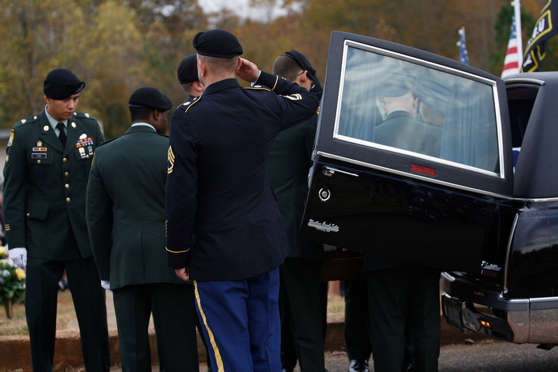The Honor Guard takes hold of Staff SGT Chris Newman's casket.