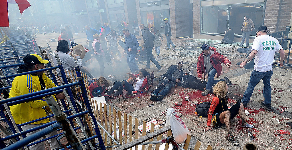. Injured people and debris lie on the sidewalk near the Boston Marathon finish line following an explosion in Boston, Monday, April 15, 2013. (AP Photo/MetroWest Daily News, Ken McGagh)