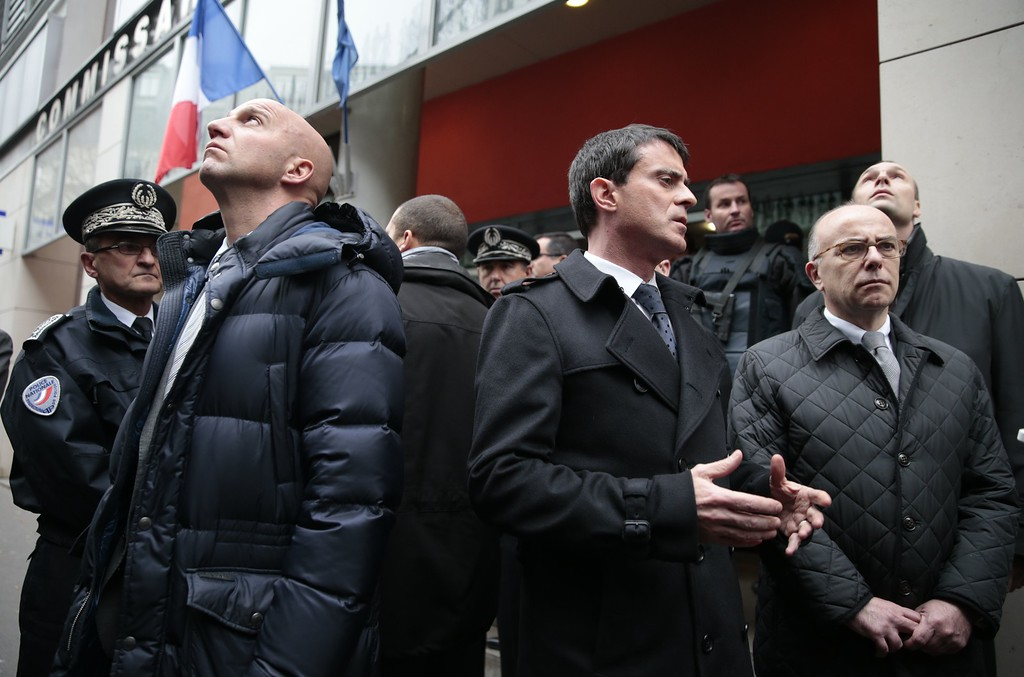. French Prime Minister Manuel Valls (C) talks with Interior minister Bernard Cazeneuve outside the 11th district police headquarters in Paris on January 7, 2015 after heavily armed gunmen shouting Islamist slogans stormed a Paris satirical newspaper office and shot dead at least 12 people in the deadliest attack in France in four decades. Police launched a massive manhunt for the masked attackers who reportedly hijacked a car and sped off, running over a pedestrian and shooting at officers.   AFP PHOTO / JOEL SAGET/AFP/Getty Images