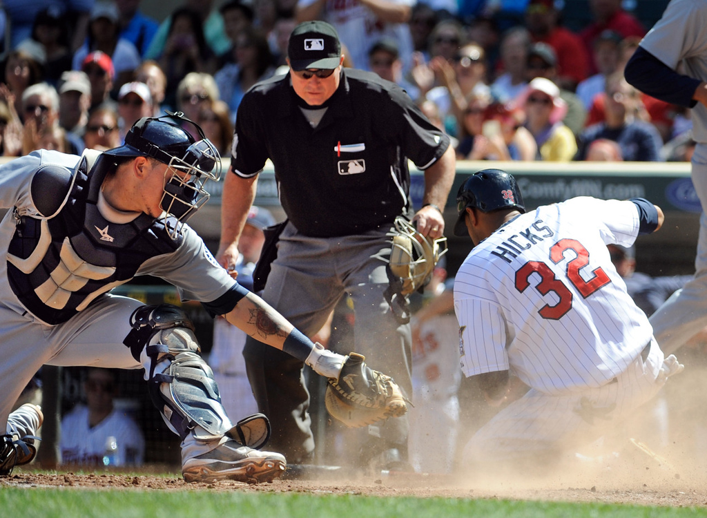. Twins base runner Aaron Hicks, right, is safe at home before Mariners catcher Jesus Sucre can make the tag as umpire Marvin Hudson looks on during the seventh inning. Hicks scored on a single by teammate Eduardo Escobar. (AP Photo/Craig Lassig)