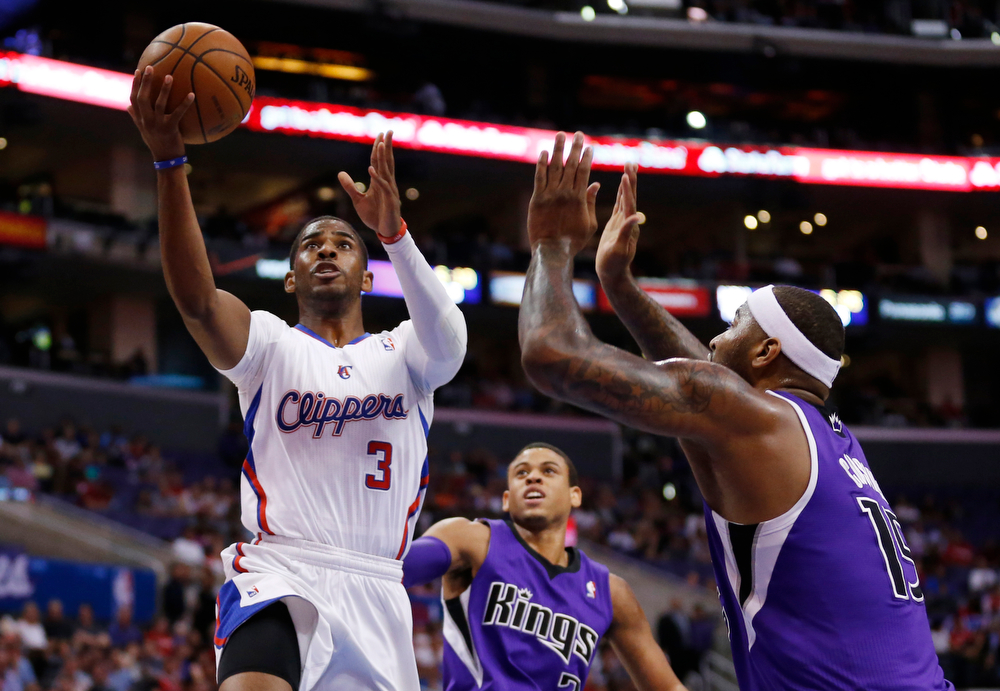 . Los Angeles Clippers guard Chris Paul shoots the ball in front of Sacramento Kings guard Ray McCallum, center, and Kings center DeMarcus Cousins, right, during the first half of an NBA basketball game in Los Angeles, Sunday, April 12, 2014. (AP Photo/Danny Moloshok)