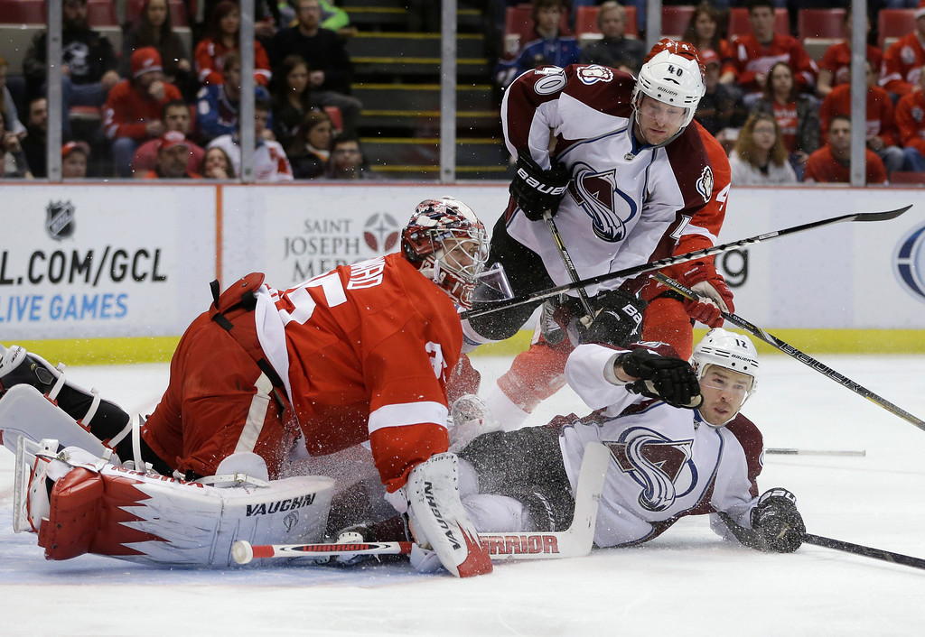 . Colorado Avalanche right wing Chuck Kobasew (12) slides into Detroit Red Wings goalie Jimmy Howard (35) during the first period of an NHL hockey game in Detroit, Tuesday, March 5, 2013. (AP Photo/Carlos Osorio)