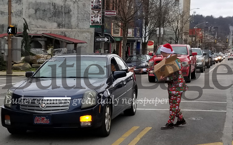 Ian Robb, son of CCR Executive Director Mike Robb, hands out cookies to passing cars on Christmas Eve along Main Street in Butler. NATHAN BOTTIGER/BUTLER EAGLE