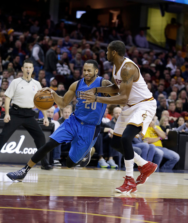 . Dallas Mavericks� Devin Harris, left, drives past Cleveland Cavaliers\' James Jones during the third quarter of an NBA basketball game Sunday, Jan. 4, 2015, in Cleveland.  (AP Photo/Tony Dejak)