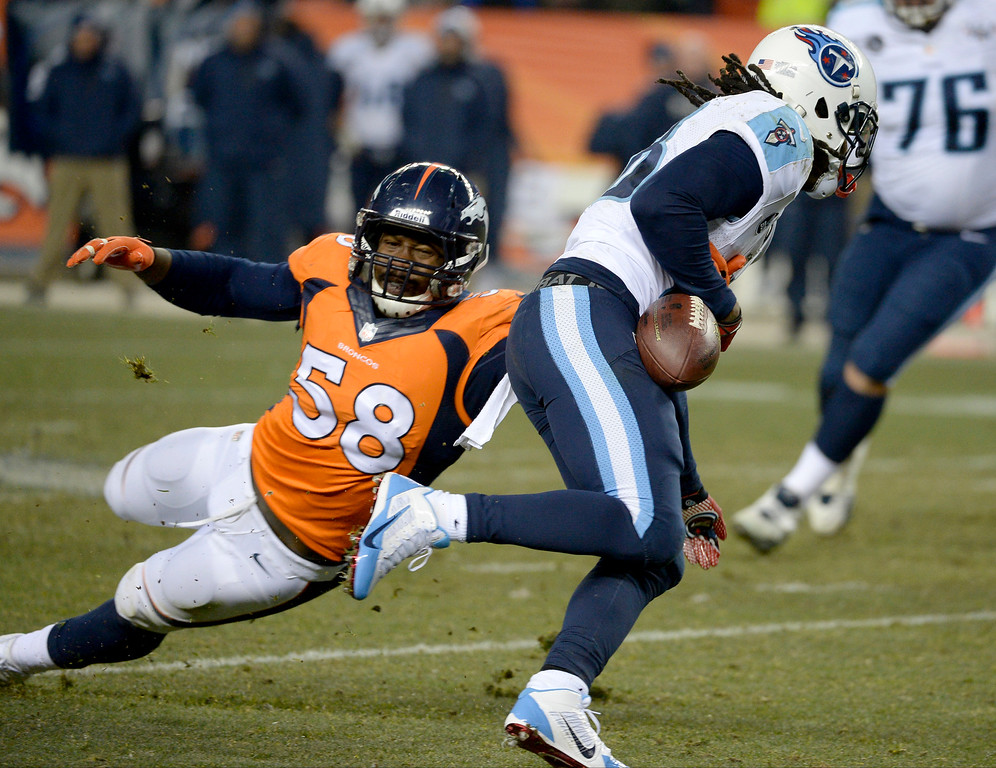 . Denver Broncos outside linebacker Von Miller (58) forces Tennessee Titans running back Chris Johnson (28) to fumble during the fourth quarter. The Broncos recovered and scored a touchdown.  (Photo by Tim Rasmussen/The Denver Post)