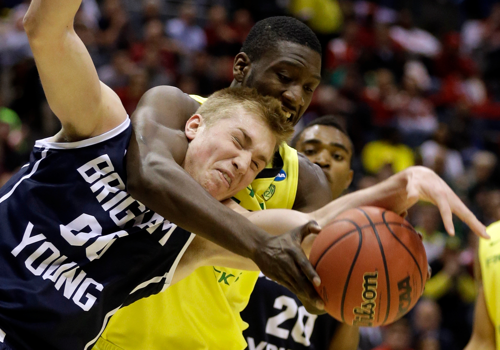 . BYU forward Eric Mika (00) and Oregon forward Richard Amardi battle for a rebound during the first half of a second-round game in the NCAA college basketball tournament Thursday, March 20, 2014, in Milwaukee. (AP Photo/Jeffrey Phelps)