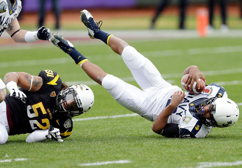 . Navy quarterback Keenan Reynolds, right, is sacked by Arizona State linebacker Carl Bradford (52) during the first half of the Fight Hunger Bowl NCAA college football game in San Francisco, Saturday, Dec. 29, 2012. (AP Photo/Marcio Jose Sanchez)
