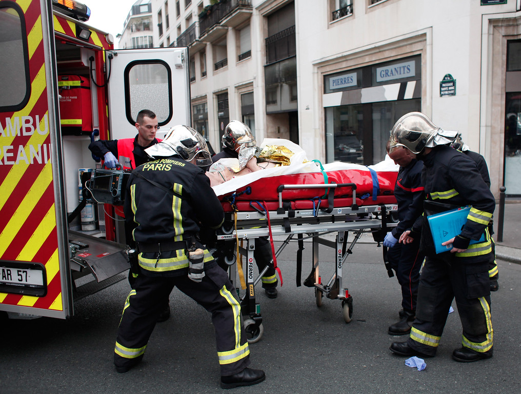 . An injured person is transported to an ambulance after a shooting, at the French satirical newspaper Charlie Hebdo\'s office, in Paris, Wednesday, Jan. 7, 2015. Masked gunmen stormed the offices of a French satirical newspaper Wednesday, killing at least 11 people before escaping, police and a witness said. The weekly has previously drawn condemnation from Muslims. (AP Photo/Thibault Camus)