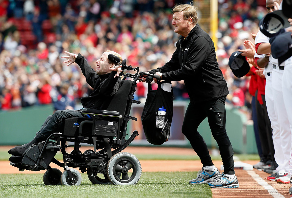 . Marathoners Dick Hoyt, right, and his son Rick come onto the field for the ceremonial first pitch before a baseball game between the Boston Red Sox and the Kansas City Royals in Boston, Saturday, April 20, 2013. Playing at home for the first time since two explosions at the Boston Marathon finish line killed three people and wounded more than 180 others, the Red Sox honored the victims and the survivors with a pregame ceremony and an emotional video of scenes from Monday\'s race. (AP Photo/Michael Dwyer)