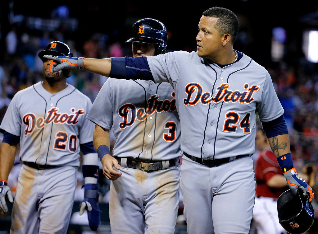 . Detroit Tigers\' Miguel Cabrera (24) points to a fan after hitting a three-run home run against the Arizona Diamondbacks during the eighth inning of a baseball game, Wednesday, July 23, 2014, in Phoenix. At left are Tigers\' Ian Kinsler (3) and Rajai Davis. (AP Photo/Matt York)