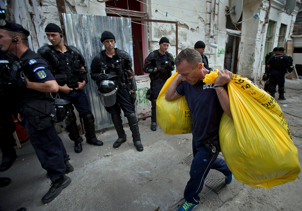 . A Roma man carries belongings as riot policemen stand by during the eviction of more than 100 people from the homes they lived in Bucharest, Romania, Monday, Sept. 15, 2014. (AP Photo/Vadim Ghirda)