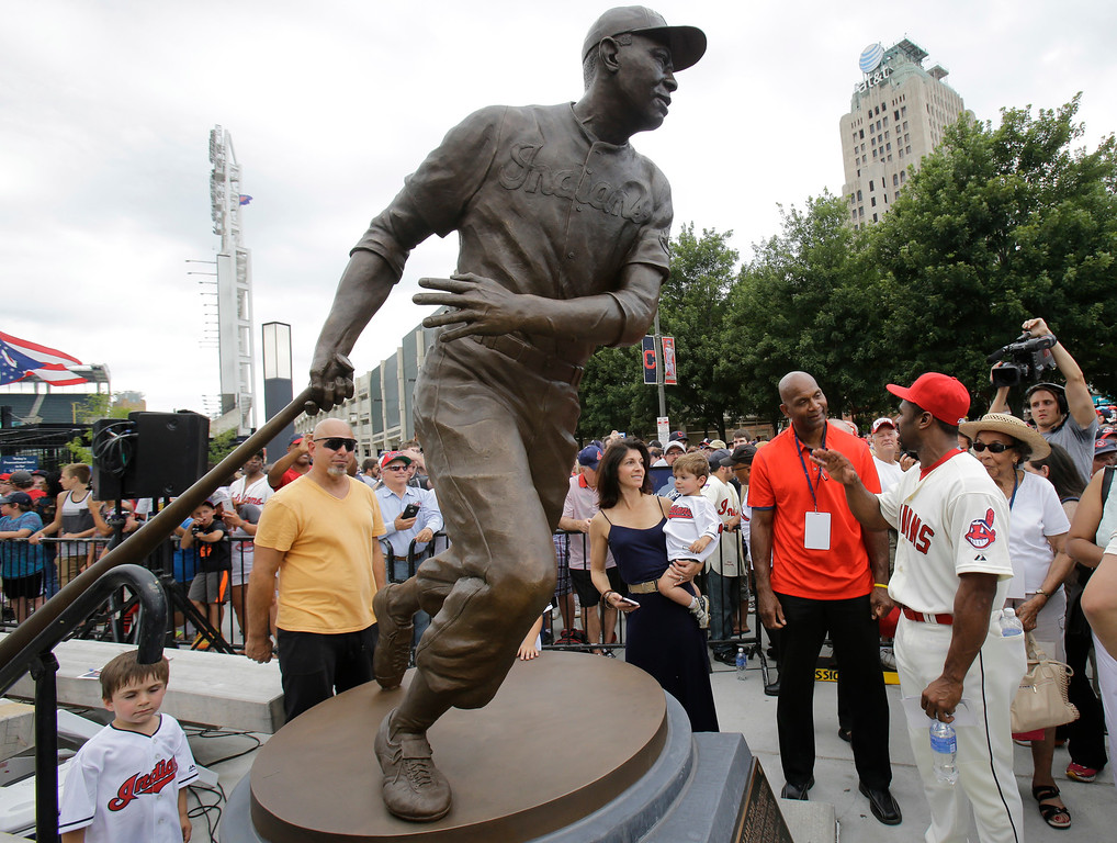. Larry Doby Jr., in red shirt, talks with Michael Bourn after the unveiling of a statue of Hall of Fame Larry Doby Saturday, July 25, 2015, in Cleveland. Doby broke the color barrier in the AL on July 5, 1947, just months after Jackie Robinson played for the Brooklyn Dodgers. Doby spent nine seasons with Cleveland and helped lead the Indians to a World Series title in 1948. He had a career .283 average with 253 homers. He led the league with 32 homers and 126 RBIs in 1954, when the Indians won 111 games. Before joining the Indians, Doby starred for Newark in the Negro League. He retired following the 1959 season. Doby\'s No. 14 was retired in 1994, 47 years after he was signed by Indians owner Bill Veeck. A seven-time All-Star, Doby died in 2003 at the age of 79. (AP Photo/Tony Dejak)
