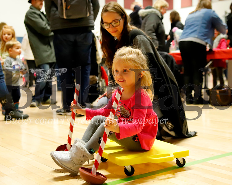 Trinity Slater,3, rolls a scooter toward a basket of candy canes, one of the games at Friday's Santa's First Stop. Seb Foltz/Butler Eagle