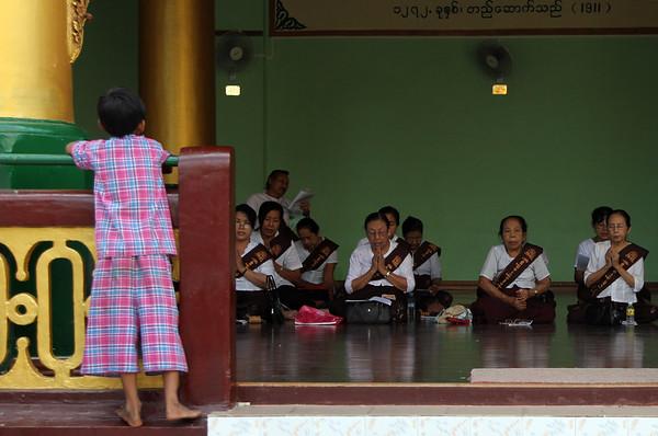 A child looks on as women chant at Shwedagon Pagoda, Rangoon (Yangon), Burma (Myanmar)