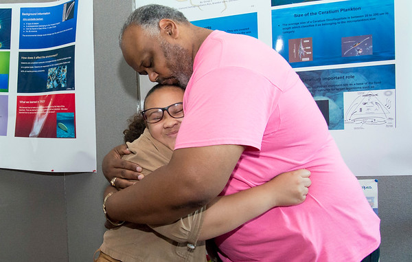 08/16/19 Wesley Bunnell | Staff TRIO, a two week long summer program run by CCSU in science and arts held their closing ceremony on Friday August 16, 2019 at Founders Hall at CCSU. Dalianiss Rios, a rising 8th grade at Betances STEM Magnet School, receives a hug and a kiss on the head from Berwyn Kelley after giving an overview of her science project hanging behind them. Kelley was invited by the family to the ceremony after working with Dalianiss previously at the New Britain Boys and Girls Club.
