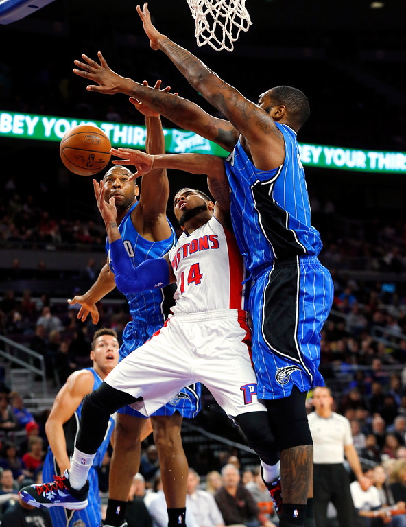 . Detroit Pistons guard D.J. Augustin (14) drives between Orlando Magic guard Willie Green, left, and Kyle O\'Quinn, right, in the second half of an NBA basketball game in Auburn Hills, Mich., Wednesday, Jan. 21, 2015. (AP Photo/Paul Sancya)
