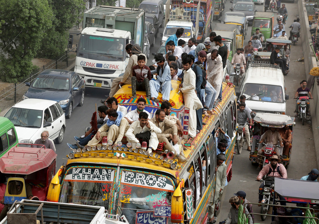 . People ride on a crowded bus to reach their villages and cities to celebrate the upcoming Eid al-Fitr Muslim holiday in Lahore, Pakistan, Thursday, June 14, 2018. (AP Photo/K.M. Chaudary)